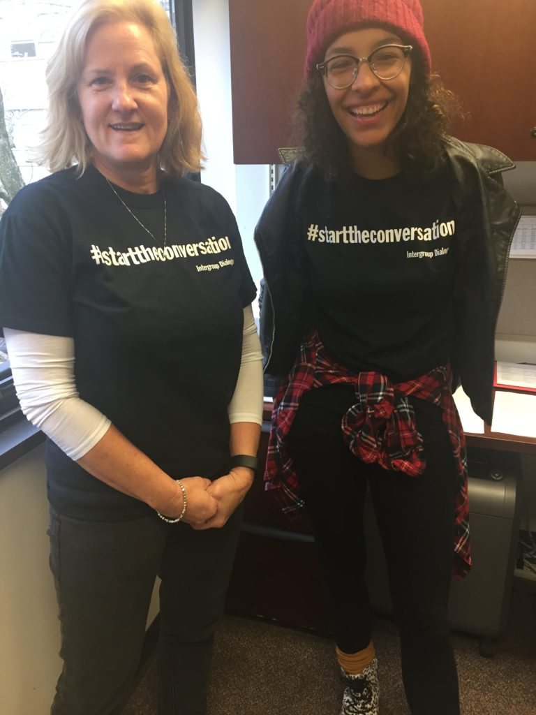Robin Higgins and Tauri Howard pose in shirts reading hashtag start the conversation
